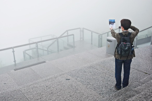 Mr. Hideyuki Uchida from Matsuyama in Japan photographs a brochure showing the view from mount Fløien the way it's supposed to be. Mr. Uchida onlys has nine days for all three of the Nordic countries, leaving him with no time to wait for the fog to clear.